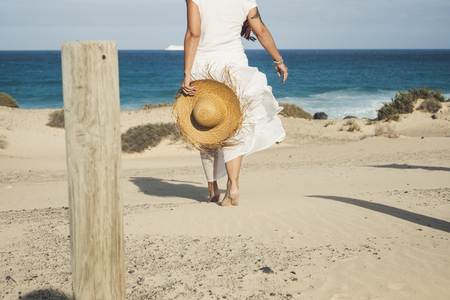 Elegant fashion lady in white dress and natural hat walking to the beach barefoot enjoying the summer holiday vacation day in tropical place - blue sea and sky horizon in background - free happy peopl 写真素材