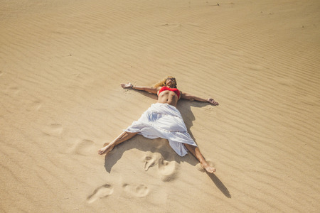 Beautiful caucasian woman enjoying summer holiday vacation travel lay down at the beach on the sand dunes having a sunbath - freedom and happiness lifestyle people outdoor in the nature 写真素材