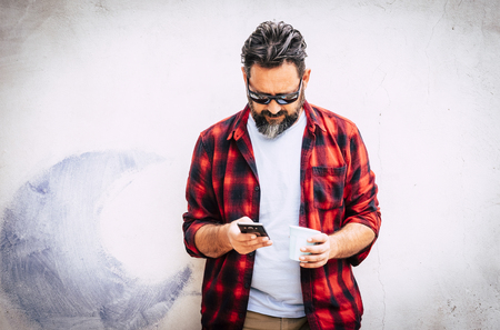 Hipster young caucasian man with beard and red shirt looking at the phone for messages or friends call - technology for senior people outdoor - white wall in background 写真素材