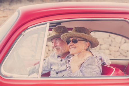 nice adult couple hug and love inside a red old vintage car parked on the road. smiles and have fun traveling together. happiness and lifestyle for nice people. summer time and vacation journey