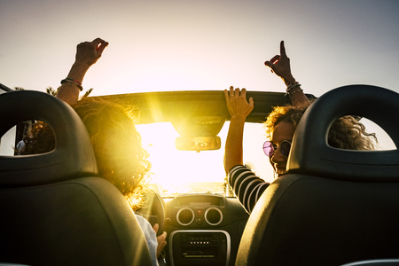 People joy and happy driving and traveling for summer holiday vacation and outdoor leisure activity with convertivle car laughing and dancing like crazy - sunlight in the glass and travel concept