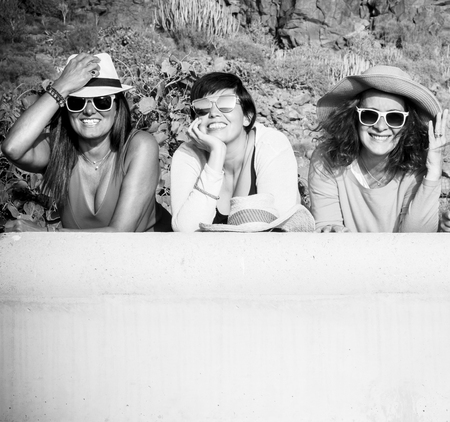 Black and white picture with three cheerful happy caucasian people young women smiling and looking at the camera in outdoor friendship activity
