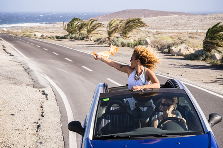 Travel and happy freedom lifestyle young people concept with couple of curly nice ladies traveling and enjoying the trip on a blue convertible car with tropical desert and sea in background 写真素材