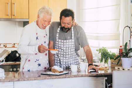 Caucasian couple at home preparing a cake together - father and son adult and senior working in the kitchen - cooking men chef at work with joy and happiness