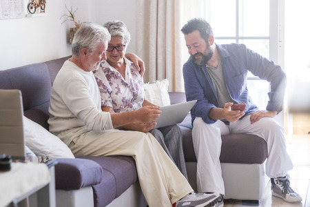 Adult and senior family at home with parents and son - caucasian people sitting on the sofa working with technology devices laptop and phone together enjoying internet connection