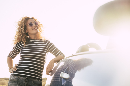 Beautiful curly blonde cute middle age woman in outdoor happy activity looking at the sun during a bright golden sunset - caucasian female with convertible car for vacation concept