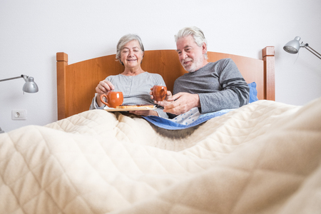 Old senior mature caucasian couple enjoy breakfast in the morning at bed in the bedroom at home - retired people live together and eat healthy food to start the day with energy