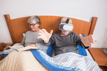 Happy alternative funny old senior couple of caucasian people grandfathers enjoy in the berdroom - man with goggles headset play virtual games and woman read a book 写真素材