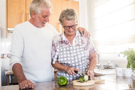 Happy real couple in love adult senior people retired man and woman enjoying the home activity in the kitchen cutting vegetables to eat healthy food for health - bright people cooking
