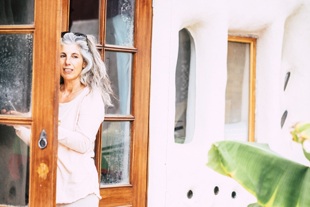 Silver society adult people caucasian woman with long white hair looking outside home from open door - alternative diversity people concept - portrait of pretty aged female 写真素材