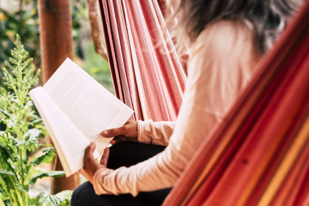 Reading a paper book old style concept to relax and study - aged caucsian woman with white hair sitting on an hammock outdoor enjoy the leisure activity