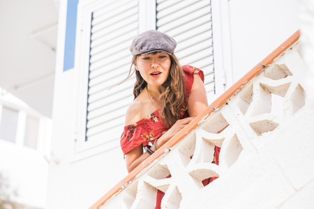 Fashion trendy young beautiful caucasian woman outside home with red dress and grey hat - smile and enjoying the leisure activity with white background wall