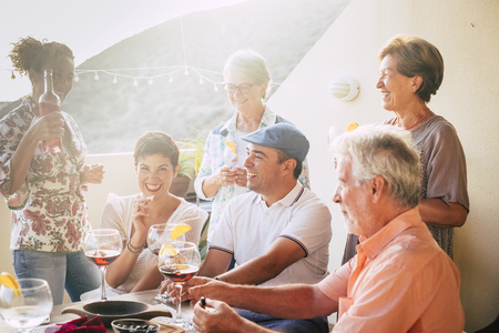 Cheerful different ages people stay together for lunch and drinking wine having a lot of fun - group of caucasian people laughing - mature adult and young - sunny backlight in outdoor terrace - food a