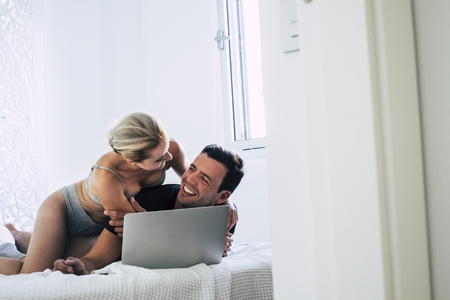 Attractive young woman and handsome boy have fun at home in the bedroom while the man work with laptop coimputer - people and couple have fun together with love - cheerful youth 写真素材
