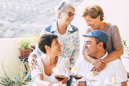 Group of caucasian friends with different ages and generations enjoy together the friendship - cheerful people with wine drinks in outdoor leisure activity - family concept