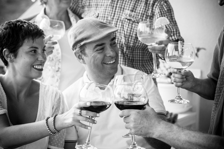 Black and white friendship people concept with couple and friends together toasting and cheering with wine red and cocktails - celebration concept  with caucasian man and woman