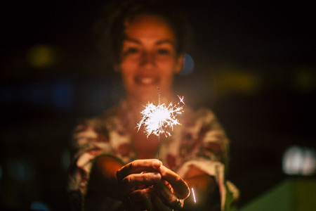 Celebration and happiness concept with cheerful woman with sparkler fire by night - new year eve motivational image - romantic and romance love atmosphere with red colors and feeling