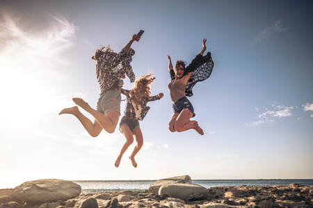 Group of young people celebrating and having fun together in friendship jumping at the beach with ocean and sunset in background - summer holiday vacation concept
