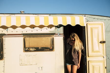 Old style american concept with beautiful blonde young girl on the door of a vintage old caravan - diversity and alternative travel style and vacation holiday adventure - freedom and tiny house