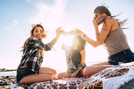 Friends people young pretty girls toasting together outdoor sitting at the beach in summer holiday vacation - friendship and women having fun with sun in backlight for sunset 写真素材