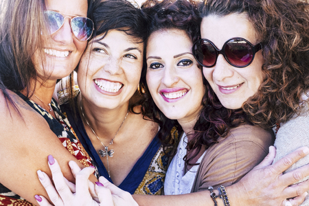 Cheerful friends happy people beautiful group of young pretty women hugging together with friendship having fun - smiles and laughs for caucasian ladies hugging eachother and enjoying the life