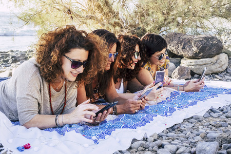 Group of trendy modern adult women all using smartphone device - cheerful people connected to internet with smartphone and friendship concept outdoor 写真素材