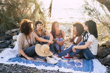 Group of young adult caucasian people women sit down in outdoor leisure activity together at the beach enjoying the sunset light in friendship - friends in beautiful place concept 写真素材