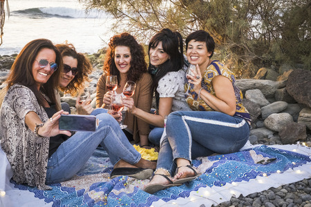 Happy group of people young adult caucasian women having fun outdoor at the beach taking selfie picture and celebrating together with red wine - ladies together laughing a lot