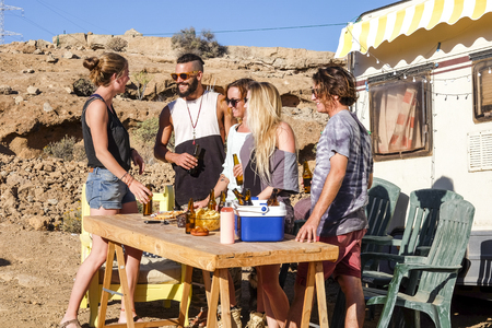 Alternative millennial home away experience workers young caucasian group of friends people outdoor in rural farm celebrating with beers and living on an old caravan tiny house 写真素材
