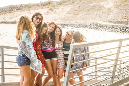 group of nice and beautiful caucasian girls young women have fun and laugh and smiles outdoor near the ocean during the sunset. backlight people enjoying the outdoor leisure activity together