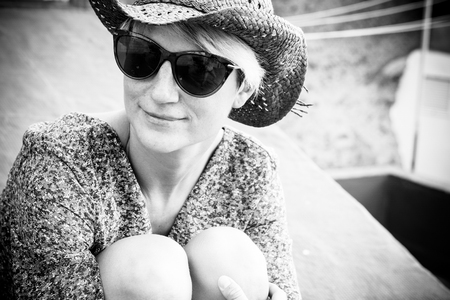 Beautiful black and white romantic portrait with blonde young caucasian woman sitting and hugging her nkees outdoor with sunglasses and little smile