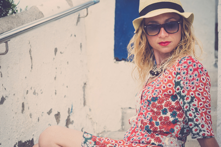 Beautiful young caucasian woman in fashion style coloured dress pose and relax - summer style with sunglasses and hat for trendy people outdoor
