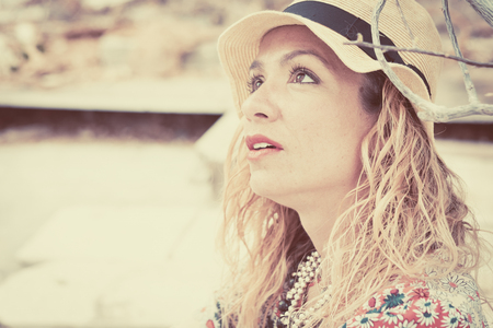 Beautiful young adult caucasian lady with trendy hat and dress look up - beautiful woman portrait in vintage colors filter - defocused background