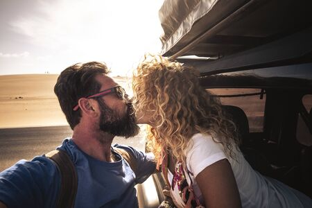 Adult caucasian cute couple of traveler kiss each other with sun in backlight - car traveling together with love and relationship - sandy desert in backgrounf and bright sky - man with beard