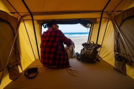 Lonely hipster traveler sitting inside a tent in free camping at the beach - relax and travel concept with alternative backpacke rlifestyle - wanderlust photographer looking the landscape Stok Fotoğraf