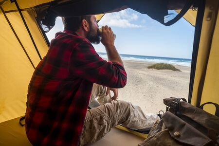 Travel and alternative hotel room destination concept with people lonely man drinking a coffee inside a tent in free camping at the beach for different lifestyle holiday vacation - enjoying freedom and ocean Stok Fotoğraf