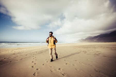 Travel and freedom adventure people man concept with wanderlust backpacker walking on the sand in a paradise beach with mountains and clouds in the background - alternative lifestyle and holiday vacation