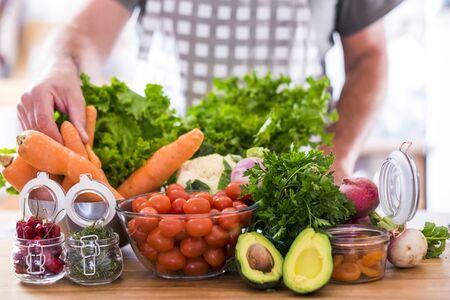 Verduras para vegetarianos o veganos o personas con estilo de vida de alimentos saludables - mezcla de colores y vitaminas en la mesa listas para ser consumidas para perder peso y salud - hombre caucásico tomando zanahorias