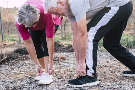 Active senior people caucasian couple doing exercises outdoor in sunny day - leisure activity for healthy retired old mature man and woman having fun together in the nature