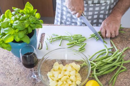 Closeup of man cutting vegetables at home cooking the lunch or dinner for family or friends - healthy lifestyle concept with vegetarian or vegan lifestyle