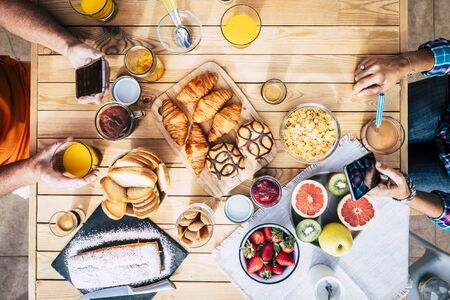 Above top view of wooden table with couple having nice breakfast in the morning with tasty cakes and fruit for different lifestyle concept - people with technology addiciton concept