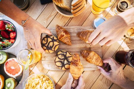 Vertical view of wooden table and people together for breakfast in friendship - brioches and cakes and fruit to start the day - happy lifestyle concept with hands taking delicious Stok Fotoğraf