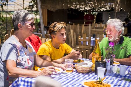 Active senior aged old people with grandson having lunh together outdoor in alternative restaurant - family concept with teenager and grandfathers together having fun - outdoor leisure activity concept
