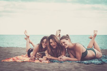 group of three beautiful girls in friendship people lay down relaxed at the beach smiling and using a smartphone together to take picture or share social media post about summer holiday vacation Stok Fotoğraf