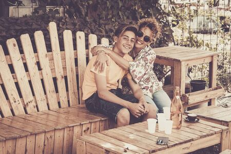 mother and son hugging with smile and enjoy leisure time together with love. family teenager boy 14 years old and mom 43 have fun sitting on a wodd bench outdoor in a sunny day. happiness family concept Stok Fotoğraf