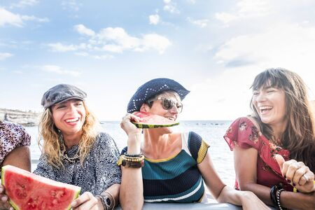 Cheerful beautiful young ladies laugh and have fun together in friendship outdoor with sea in background and eating red watermelon - summer holiday vacation concept for women