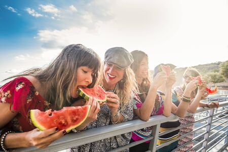 Cheerful group of people females friends having fun together in summer outdoor leisure activity eating fresh and diet red watermelon with laughs - Young women laughing and smilng