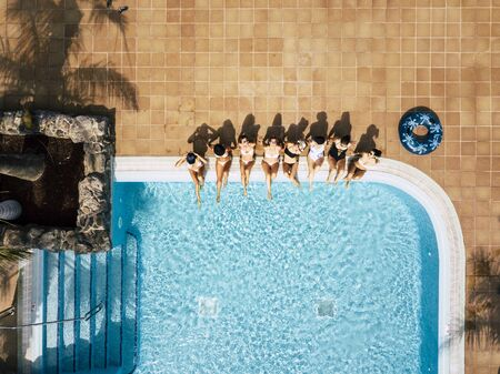 Friends females caucasian people enjoying the swimming pool in summer holiday vacation at hotel or resort - high top vertical view of young women sit down at the poolside in friendship together Stok Fotoğraf