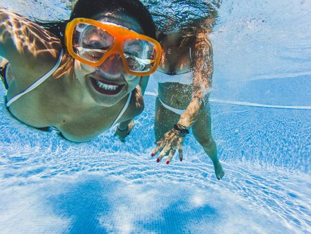Cheerful happy beautiful people caucasian girl smiling underwater with friend - travel and play in the blue water pool together - joy lifestyle for couple of females friends enjoying summer Stok Fotoğraf
