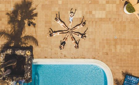Vertical top view of group of women young friends compose a star together with their bodies - concept of summer people vacation lifestyle and friendship together - beautiful background hotel pool Stok Fotoğraf